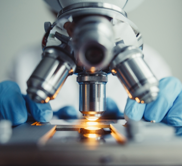 Close up of a lab technician positioning a glass slide on a microscope